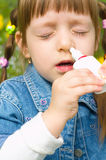 Girl spraying nose. Little girl spraying her nose outdoors Royalty Free Stock Photography