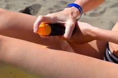 Girl spraying sunscreen Stock Photography
