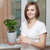 Girl sprays a house plant Royalty Free Stock Photos