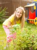 Girl sprays plants in the garden Stock Photo