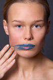 A girl spread blue lipstick Royalty Free Stock Image