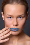 A girl spread blue lipstick Stock Image