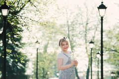 Girl with a sprig of cherry blossoms in her hands. She enjoys th royalty free stock photography