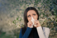 Girl with Spring Allergies in Floral Decor. Portrait of a sick woman blowing her nose Stock Photography
