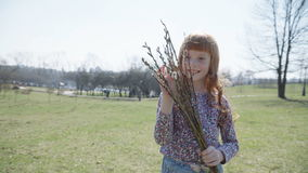Girl with a spring bunch. Cute ginger girl in the park with a spring bunch of branches, steadicam shot stock video