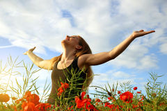 Girl in spring field. With poppies Royalty Free Stock Photo