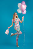 Girl in spring overalls with balloons, carefree mood royalty free stock photography