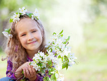 Girl at spring park. Little girl with branches blossoming apple tree Stock Photo
