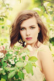 Girl in Spring Park. Fashion Model Woman on Flowers. Cute Girl in Spring Park. Fashion Model Woman on Flowers and Green Leaves Background Royalty Free Stock Images