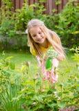 Girl sprinkles rose in the garden Royalty Free Stock Photo