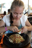 Girl sprinkles spaghetti with cheese Stock Images
