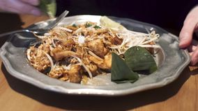 Girl sprinkles sugar on famous Thai dish - Pad Thai with noodles, chicken, tofu, tamarind sauce, soy sprouts.
