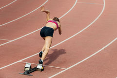 Girl sprinter start at 400 meters. Girl sprinter at start of 400 metres at stadium Royalty Free Stock Image