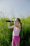 Girl with spyglass Stock Images