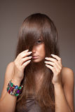 Girl spying. Portrait of beautiful girl with shy look and long hair Stock Photo