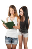 Girl spying on girlfriend  reading a book Royalty Free Stock Image