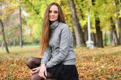 The girl squats in autumn wood in shining sun beams stock photo