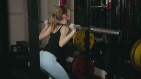 The girl squats with a barbell. Young girl with white hair in black tank top and blue tights doing squats with a vulture from a barbell in a dark fitness club stock footage