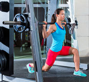 Girl squats in multipower squatting smith machine. Barbell at gym smith Royalty Free Stock Photography