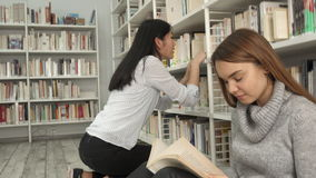 Girl squats near the book rack at the library stock footage