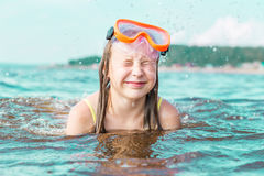The girl squeezed her eyes shut from the sea spray Stock Image