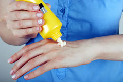Girl squeezes cream on the hand Royalty Free Stock Image