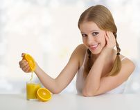 Girl squeezes the juice from the orange Stock Photo