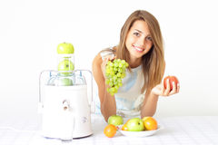 Girl Squeezes The Juice From The Juicer Royalty Free Stock Photo