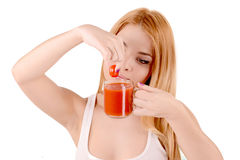 Girl squeezes of tomato juice. Girl with a little tomato and tomato juice, a healthy lifestyle stock image