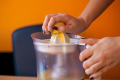 Girl squeezing a lemon with an electric citrus juicer royalty free stock photo