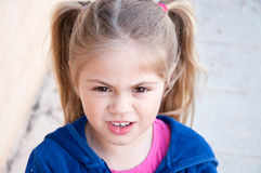Girl squinting eyes. Little girl squinting her eyes Stock Photo