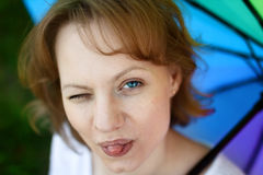 Girl is squinting and showing tongue. Portrait of funny girl which is having fun and showing tongue, one eye is squinted, on multicolored umbrella background Royalty Free Stock Photo