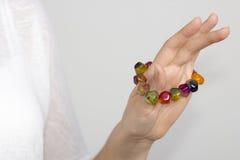 Girl'ss hand med det mång- färgarmbandet royaltyfri bild