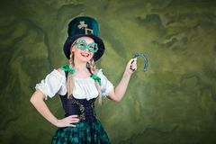 A girl in a St. Patrick costume with a horseshoe in hands. A girl in a St. Patrick costume with a horseshoe in hands smiles on a green background. St. Patrick`s Stock Photos