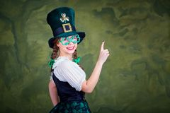 A girl in a St. Patrick costume is smiling. A girl in a St. Patrick costume is smiling on a green background Stock Images