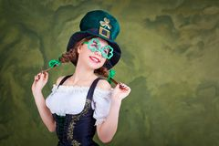 A girl in a St. Patrick costume is smiling. A girl in a St. Patrick costume is smiling on a green background Royalty Free Stock Images