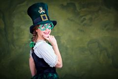 A girl in a St. Patrick costume is smiling. A girl in a St. Patrick costume is smiling on a green background Stock Photo