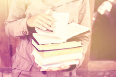 Girl with stack of books, vintage color effect Stock Photo