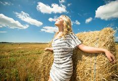 Girl at a stack of straw Royalty Free Stock Photos