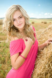 Girl at a stack of straw Royalty Free Stock Images