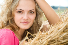 Girl at a stack of straw Stock Photo