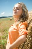 Girl at a stack of straw Stock Images