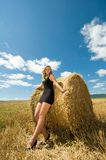 Girl at a stack of straw Royalty Free Stock Photography