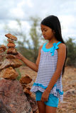 Girl stacking rocks Royalty Free Stock Photos