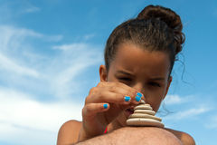 Girl stacking stones Royalty Free Stock Image