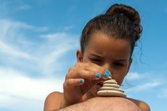 Girl stacking stones Royalty Free Stock Image