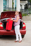 Girl stacks a suitcase. In a car luggage carrier Royalty Free Stock Photo