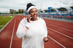 Girl on stadium. Happy young active woman in sportswear talking by smartphone while training on stadium Royalty Free Stock Photo