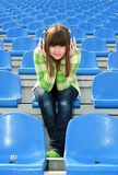 Girl at the stadium listening music Stock Image