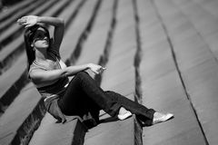 Girl on the stairs. Girl in jeans is sitting on the stairs and shuting from the sun Royalty Free Stock Photos